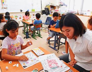 色塗りや紙の切り貼りで英語を勉強する小学1年生=31日、宜野湾市のアメラジアンスクール・イン・オキナワ
