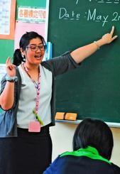 1年生に優しく英語を教えるデヴィ・ラティ・ガヤトリさん=2日、沖縄市・宮里中学校