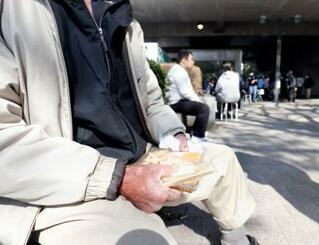 NPO法人が開いた生活相談会に参加し、提供された食事を手にする男性=4日午後、東京都新宿区