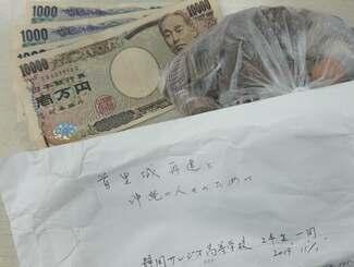 静岡サレジオ高校の修学旅行生が首里城再建のために沖縄タイムス社に託した寄付=1日、沖縄タイムス社