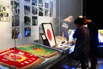 沖縄の高校球史を彩る展示物に見入る来場者たち=9日、県立博物館・美術館