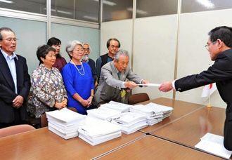 土砂採取に反対する全国からの署名を内閣府へ提出する大津幸夫共同代表(右から2人目)=15日、東京・内閣府