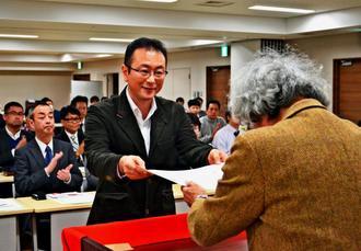 鎌田慧さんから賞状を受け取る鈴木実記者=23日、東京・台東区民会館