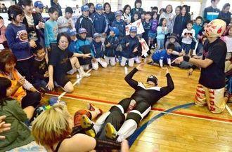 熱戦は場外乱闘にもつれこみ、子どもたちはくぎ付け=11日午前、豊見城市・上田小学校(伊藤桃子撮影)