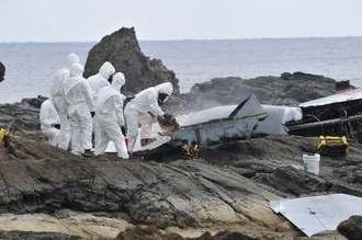 リーフに打ち上げられたオスプレイ尾翼部分の解体作業をする米軍関係者=16日午後1時47分、名護市安部の海岸