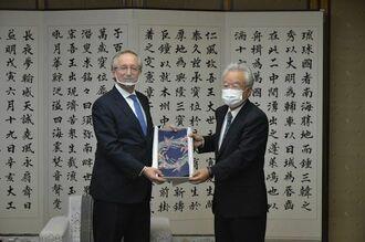 ガルージン駐日ロシア大使(左)と会談し、記念品を手渡す富川盛武副知事=10日、沖縄県庁