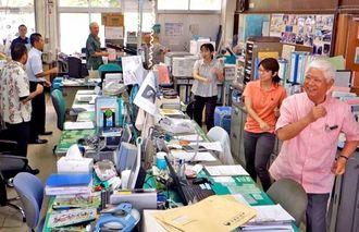 曲に合わせ笑顔で踊る島袋村長(右)と職員たち=3日午後3時ごろ、大宜味村役場