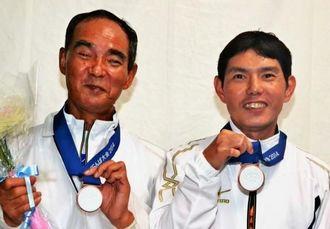 銅メダルを手に喜ぶ田場上さん(左)、島袋忠さん