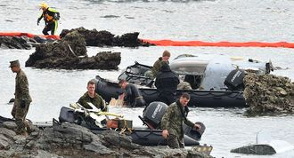 オスプレイの機体の残がいを回収する米兵=15日午後1時、名護市安部の海岸(渡辺奈々撮影)