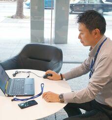 専用のパソコンやUSBデバイスを使って職場外でリモートワークをする男性=28日、那覇市