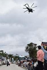 N1地区出入り口前に座り込む市民らの上空を飛ぶ米軍ヘリ=23日午前9時55分、東村高江