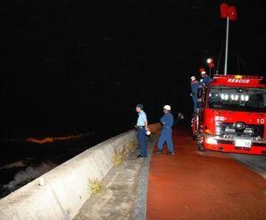 ライトで海上を照らし捜索を続ける消防隊員ら。時折、旧道まで波しぶきが上がった=5日午後8時28分、国頭村与那