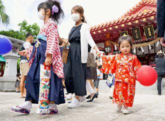 七五三詣の後、千歳あめと風船を手に歩く女の子たち=15日午前、那覇市若狭・波上宮(下地広也撮影)