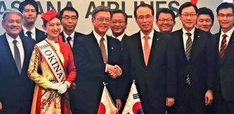 翁長雄志知事(前列左から3人目)と握手するアシアナ航空のチョ・ギュヨン副社長(同4人目)=日、韓国