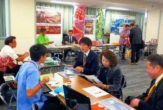 修学旅行向けの宿泊施設や体験型施設のブースで説明を受ける来場者ら=3日、千代田区・東京交通会館