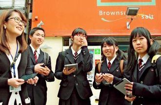 タブレット端末に表示された新聞記事などを見ながら、街歩きを楽しむ静岡・裾野高校の生徒=29日、那覇市の国際通り