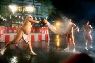 川原湯温泉の「湯かけ祭り」で、湯をかけ合うふんどし姿の男たち=20日早朝、群馬県長野原町