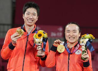 混合ダブルスで獲得した金メダルを手にし、笑顔を見せる水谷隼(左)、伊藤美誠組=東京体育館