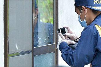 銃弾が貫通したガラス戸の写真を撮る県警鑑識職員