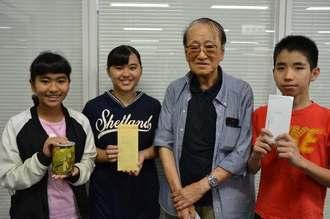 沖縄こども未来プロジェクトに寄付した(左から)上江洲亜依さん、亜耶さん、隆さん、喜屋武涼真君=26日、沖縄タイムス社