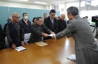 県につり下げ訓練の中止などを求める要請書を手渡す崎濱秀正区長(左から2人目)=12日午後、県庁