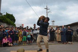 雨を願い60キロはあるとされるカンドーラ―石を持ち上げる小浜島の青年=竹富町小浜