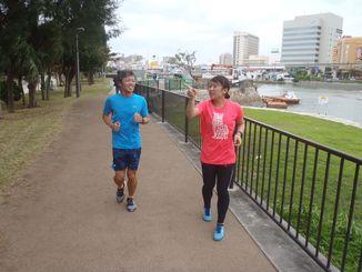 スタッフ(右)からアドバイスを受け走る記者=那覇市・奥武山公園