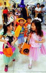カラフルな衣装で、店内をパレードするオキナワインターナショナルスクールの子どもたち=那覇市金城・イオン那覇店