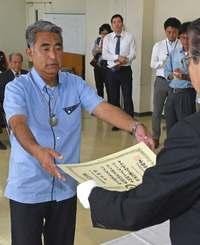 県選管の当山尚幸委員長(右)から当選証書を受け取る屋良朝博氏=24日午前、県庁