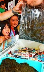 人気の詰め放題。袋いっぱいのモズクに驚く子どもたち=11日、タイムスビル1階エントランス