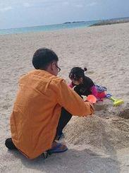 休日に砂遊びをする山里卓さんと娘の夏凜ちゃん=豊見城市の美らSUNビーチ(提供)