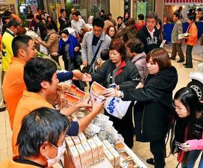 島の特産品を買い求める多くの来場者でにぎわう即売会場=21日、那覇市久茂地・タイムスビル
