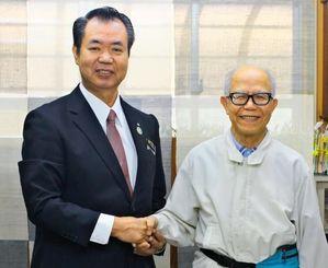 川満町長(左)から就任を歓迎され、握手を交わす久保利夫医師(竹富町役場提供)