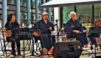 「二見情話」を演奏中のパリ三線クラブのフロリアン・ブリカールさん(中央)と本間彩さん(左)=ロンドン東部スピタルフィールズ