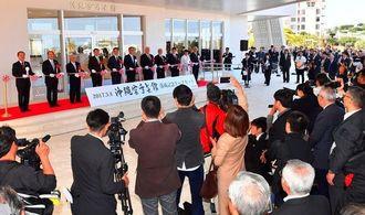 大勢の参列者が見守る中、沖縄空手会館の開館を祝いテープカットする関係者(金城健太撮影)