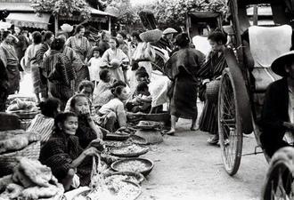 戦前に現在の那覇市東町にあった「那覇ウフマチ(大市)」と呼ばれた市場の様子。立ち並ぶ建物の中に店を設けて品物を売るほか、路上で商品を並べて露店販売をする人々もおり、庶民生活の場としてにぎわった。띱 市場では品物ごとに販売場所が分かれており、魚・肉・米・乾物等を販売する区域や、野菜・芋・雑貨を売る店舗などがあった。背後の建物には「大迫商店」の店名が確認できる。残された当時の地図と照合すると、野菜や雑貨を販売していた通り沿いから、海産物などを販売する「大迫海産」の店先を撮影したものと思われる。띱 写真では女性たちが野外で「バーキ」と呼ばれる竹かごに穀物や農作物のようなものを販売している姿のほか