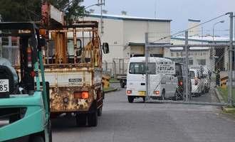 着陸帯の改修工事のため基地内に入る関係車両=22日午前7時55分ごろ、伊江村・米軍伊江島補助飛行場ゲート前
