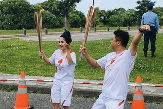聖火リレーで沖縄の文化を発信しようとウチナーカンプー姿でカチャーシーを踊りながらトーチキスをするランナーたち=1日、名護市民会館周辺