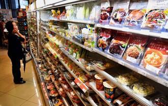 ずらりと並んだ総菜に見入る買い物客=9日、那覇市内のコンビニエンスストア