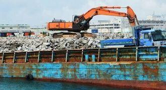 奄美大島から到着した石材。台船から陸に一時保管するためトラックに積まれる=14日、那覇新港ふ頭