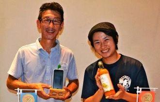 来場者から評価されたスピーカースタンドを手にする荒木さん(左)とパッションフルーツジュース100%を持つ橋爪さん=石垣市民会館