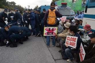 工事車両を基地内に通すため、ゲート前に座り込む市民らを強制排除する機動隊員=25日午前9時、名護市辺野古の米軍キャンプ・シュワブゲート前
