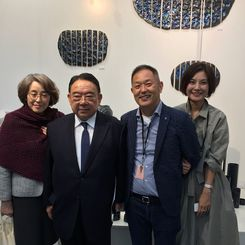 夫人と写真に納まる金子晴彦さん(右から2人目)、木寺昌人大使(同3人目)=グランパレ展示会場の石垣焼ブース