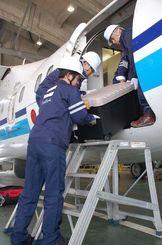 アンテナなどの入った災害応急資機材を海保の中型機に詰め込むソフトバンクの職員ら=16日、那覇空港