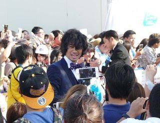 沖縄国際映画祭のレッドカーペットでファンに笑顔を見せる斎藤工さん=21日午後、那覇市・波の上うみそら公園