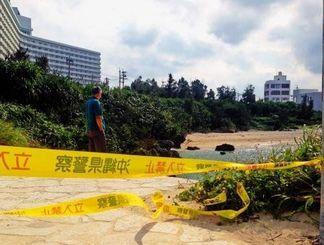 日課の散歩中に、幼子2人が亡くなった現場で立ち止まり、海岸を見詰める地元住民=17日午前9時45分ごろ、読谷村宇座