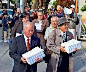 3万9826人の署名を持って那覇地裁に入る山内徳信共同代表(左)ら=17日午後2時58分ごろ、那覇地裁前