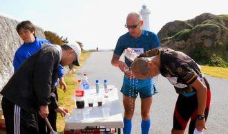 75キロ地点で疲れを隠せない選手たちに給水するボランティア=11日、宮古島市の東平安名崎
