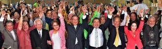 県知事選で当確が決まり万歳三唱する翁長雄志氏(中央)。新基地建設反対を訴えた翁長氏の圧勝にもかかわらず、安倍政権は新基地建設を強行する=2014年11月16日