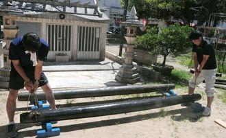 新調した2本のカナチ棒。手前がヤマグリの木、奥がクスノキ製=6日、与那原町与那原「親川」前